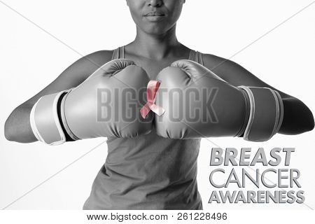 Breast cancer awareness message against woman for breast cancer awareness with ribbon in boxing gloves