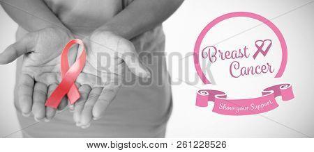 Heart shape ribbon with breast cancer text against woman holds ribbon in both hands for breast cancer awareness