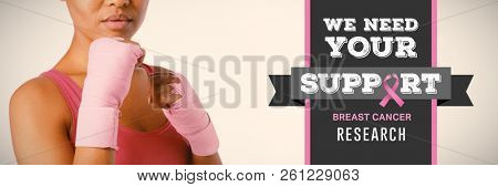 Breast cancer awareness message against mid section of woman with gloves for breast cancer awareness