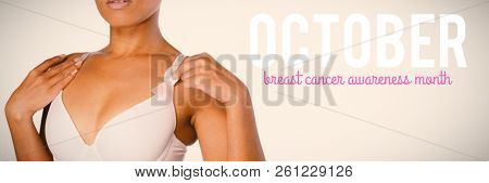 Pink breast cancer awareness text against woman for breast cancer awareness with pink ribbon