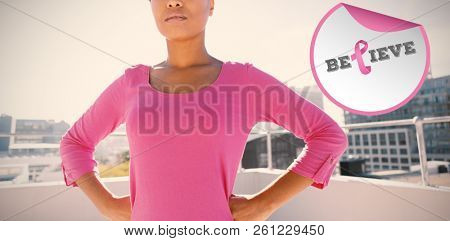 Breast cancer awareness message against serious looking woman standing confident for breast cancer awareness