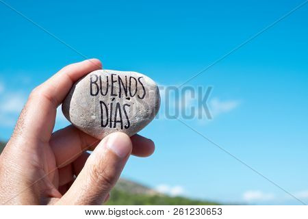 closeup of a young caucasian man showing a stone with the text buenos dias, good morning in spanish written in it, holding it against the blue sky poster