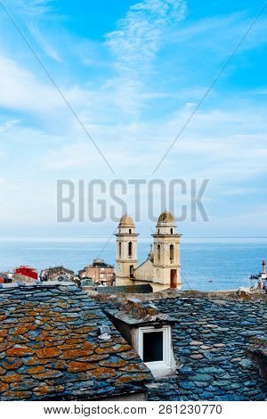 the characteristic twin bell towers of the Saint-Jean Baptiste Church in Bastia, Corsica, France, highlighting above the old slate rooftops of the old town, and the Mediterranean sea in the background