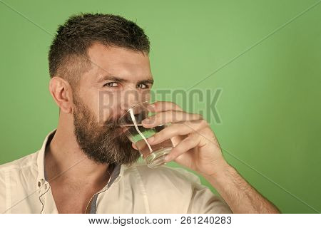 Life source and healthcare. Hangover and thirst. Man smiling with long beard hold water glass on green background. Hipster drink clean healthy water, refreshing. Health and dieting. poster