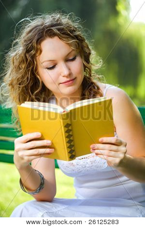 Beauty woman reading a book in park