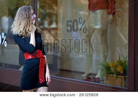 Junge Frau suchen in Schaufenstern mit Verkauf