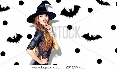Halloween Party girl in with costume celebrating. Happy Halloween Witch with bright make-up and long hair. Beautiful young surprised woman posing in witches sexy costume. Isolated on white background