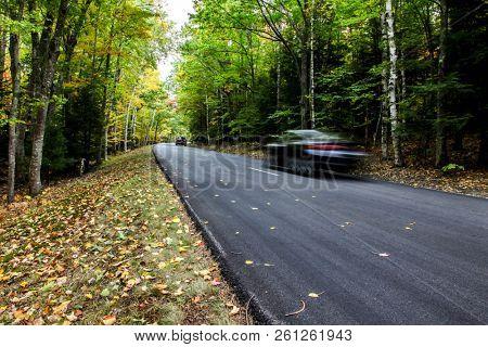Car driving thru autumn road