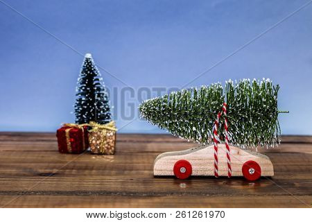 Wooden car with christmas tree and gift boxes on table top