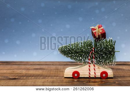 Wooden car with Christmas tree and gift box on table top