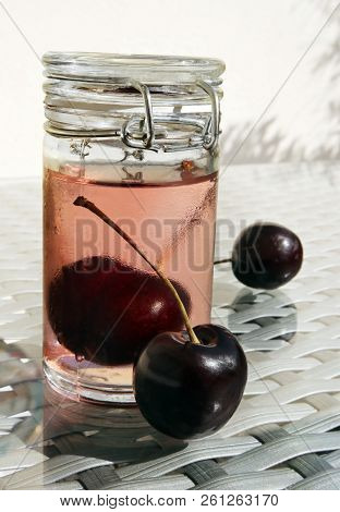 Still Life With Wild Cherries And Small Glass Jar Of Sweet Cold Compote Against A High Key Backgroun