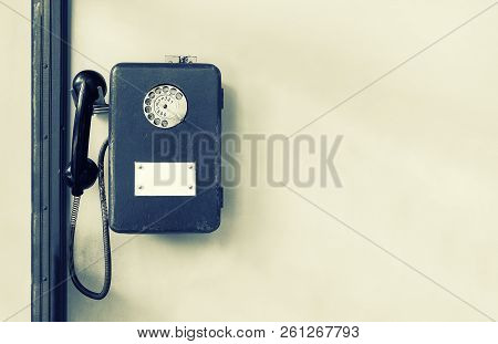 Old Public Payphone On The Wall. Brown Metal Phone. Disk Telephone.