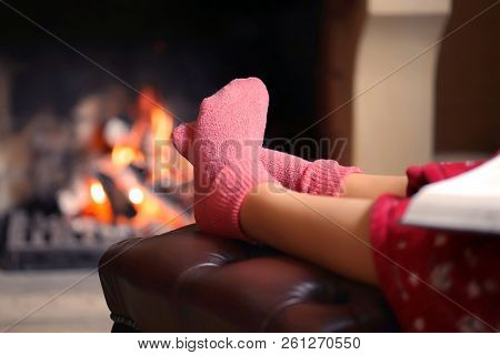 Woman Feet With Socks Sitting Near Fireplace With A Warmth Background. Woman In Warm Socks Resting N