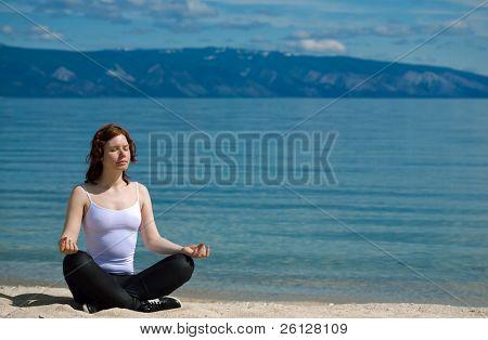Beautiful girl meditating on the background of mountains on the lake Baikal