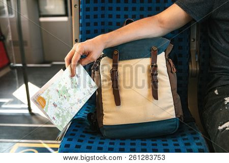 Tourist Concept. A Man Or A Boy Holds A Map In His Hand During A Trip In A Train Or A Commuter Train