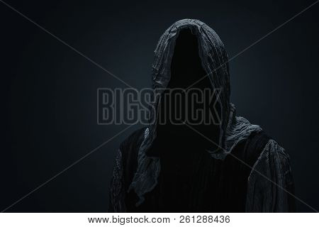 Silhouette Of A Grim Reaper Over Dark Gray Background With Copy Space