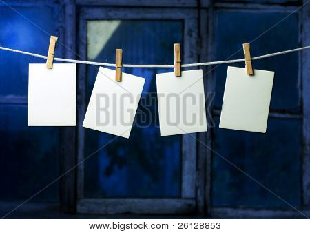 four photo paper attach to rope with clothes pins on window background