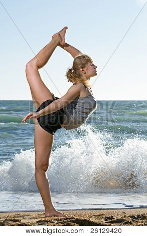 Beautiful young woman doing fitness exercise on a beach