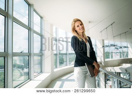 Portrait Of Young Busineswoman Standing In Office Lobby.