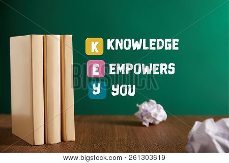 Three Books And Crumpled Papers On Wooden Table With E-learning - Learning Is Fun Lettering