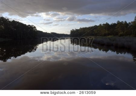 Scenic sunrise shot of the tree line in silhouette along the Neuse River in North Carolina. poster