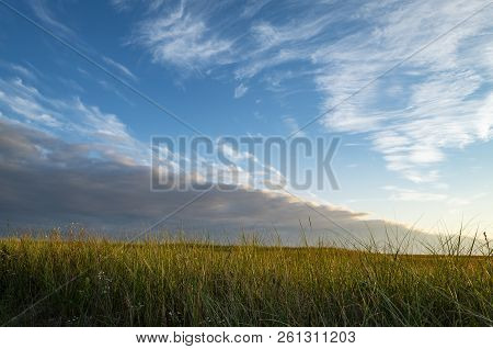 Beautiful Cloud Formation Over Tall Grass At Sunset