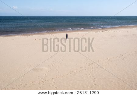 Man Walking Towards The Ocean On Brackley Beach Prince Edward Island