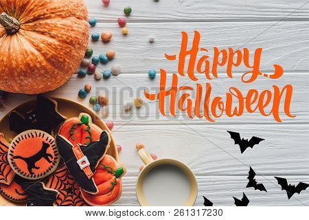 Top View Of Pumpkin, Plate With Halloween Cookies, Candies And Cup With Milk On Wooden Table With Ba