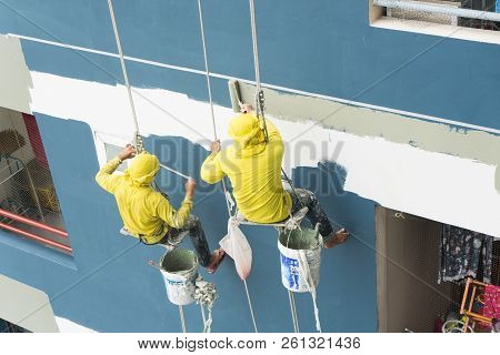 Painters Hanging On Roll, Painting Color On Building Wall. Facade Builder Worker With Roller Brush,