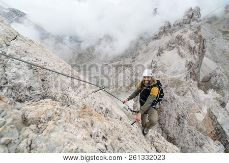 young handsome male climber on a steep and exposed rock face climbs a Via Ferrata in Alta Badia in the South Tyrol poster