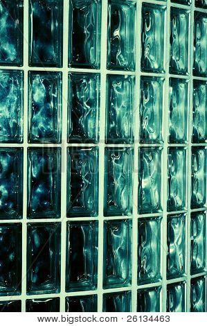 Closeup of a greenish blue glass brick wall inside a building
