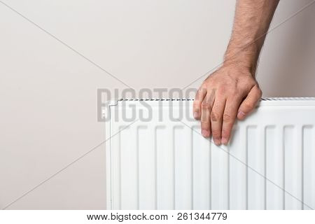 Man Warming Hand On Heating Radiator Against Color Background. Space For Text