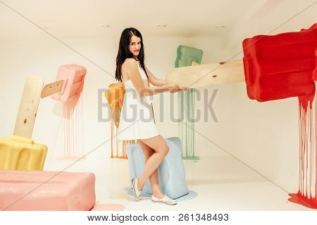 Young Beautiful Girl In White Dress Posing Next To Sweet Decors. Background From Colorful Ice Cream
