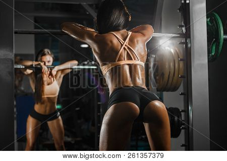 Attractive Sporty Woman Relaxing With Barbell In Gym. Beautiful Fitness Girl Resting After Sport Wor