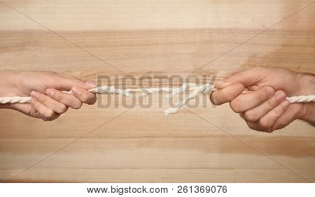 Man And Woman Pulling Frayed Rope At Breaking Point On Wooden Background