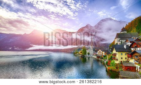 Foggy Autumnal Sunrise At Famous Hallstatt Lakeside Town Reflecting In Hallstattersee Lake. Location