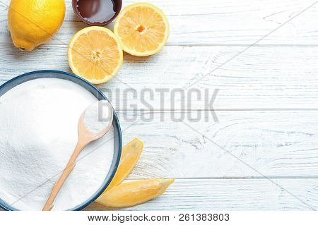 Flat Lay Composition With Baking Soda And Lemons On White Wooden Background. Space For Text