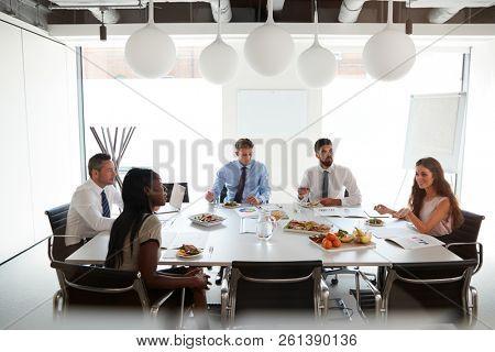 Businessmen And Businesswomen Meeting In Modern Boardroom Over Working Lunch
