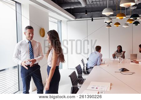 Businessman And Businesswoman Standing In Modern Boardroom Having Informal Discussion With Colleagues Meeting Around Table In Background