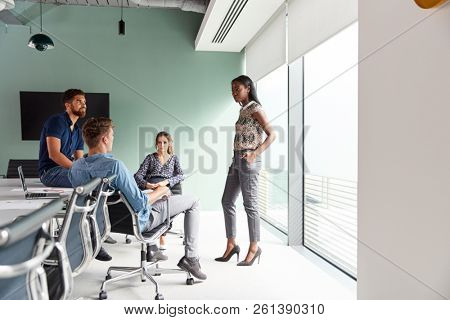 Casually Dressed Businessmen And Businesswomen Having Informal Meeting In Modern Boardroom
