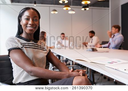 Portrait Of Businesswoman In Modern Boardroom With Colleagues Meeting Around Table In Background