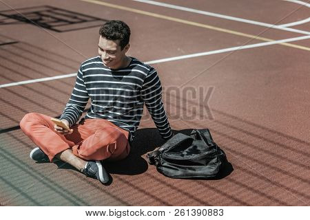 Cheerful Jovial Guy Receiving News On Ground
