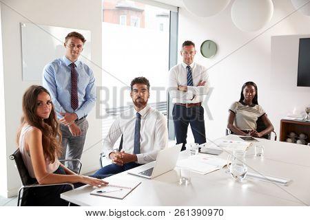 Portrait Of Businessmen And Businesswomen Meeting Around Table In Modern Boardroom