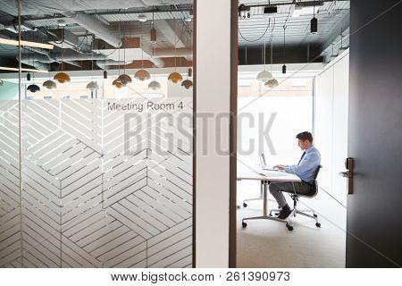 Businessman Working On Laptop At Boardroom Table Viewed Through Meeting Room Door