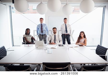 Portrait Of Businessmen And Businesswomen Meeting Around Table In Modern Boardroom poster