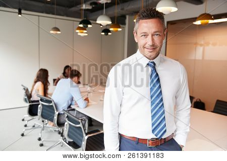 Portrait Of Mature Businessman Standing In Modern Boardroom With Colleagues Meeting Around Table In Background