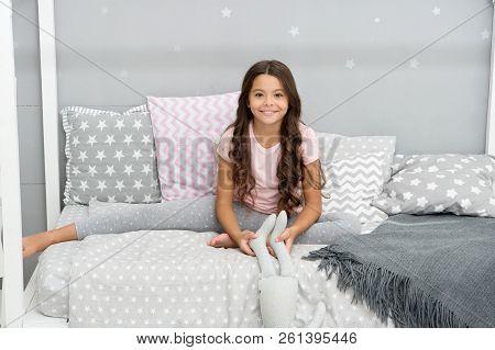 Girl Child Wear Pajamas Play Bunny Toy. Play Soft Toy Before Go Sleep. Girl Long Curly Hair Enjoy Ev