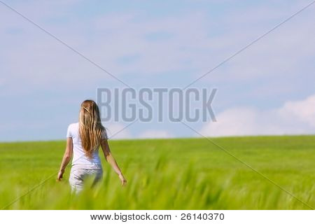 young girl going away in green field