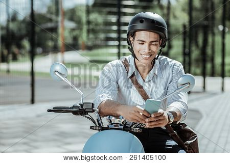 Cheerful Jovial Guy Reading Message On Motorbike