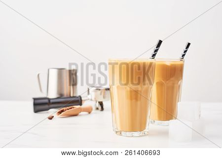 Barista Concept. Ice Coffee In A Tall Glass With Straws And Milk Pitcher, Portafilter And Wooden Cof